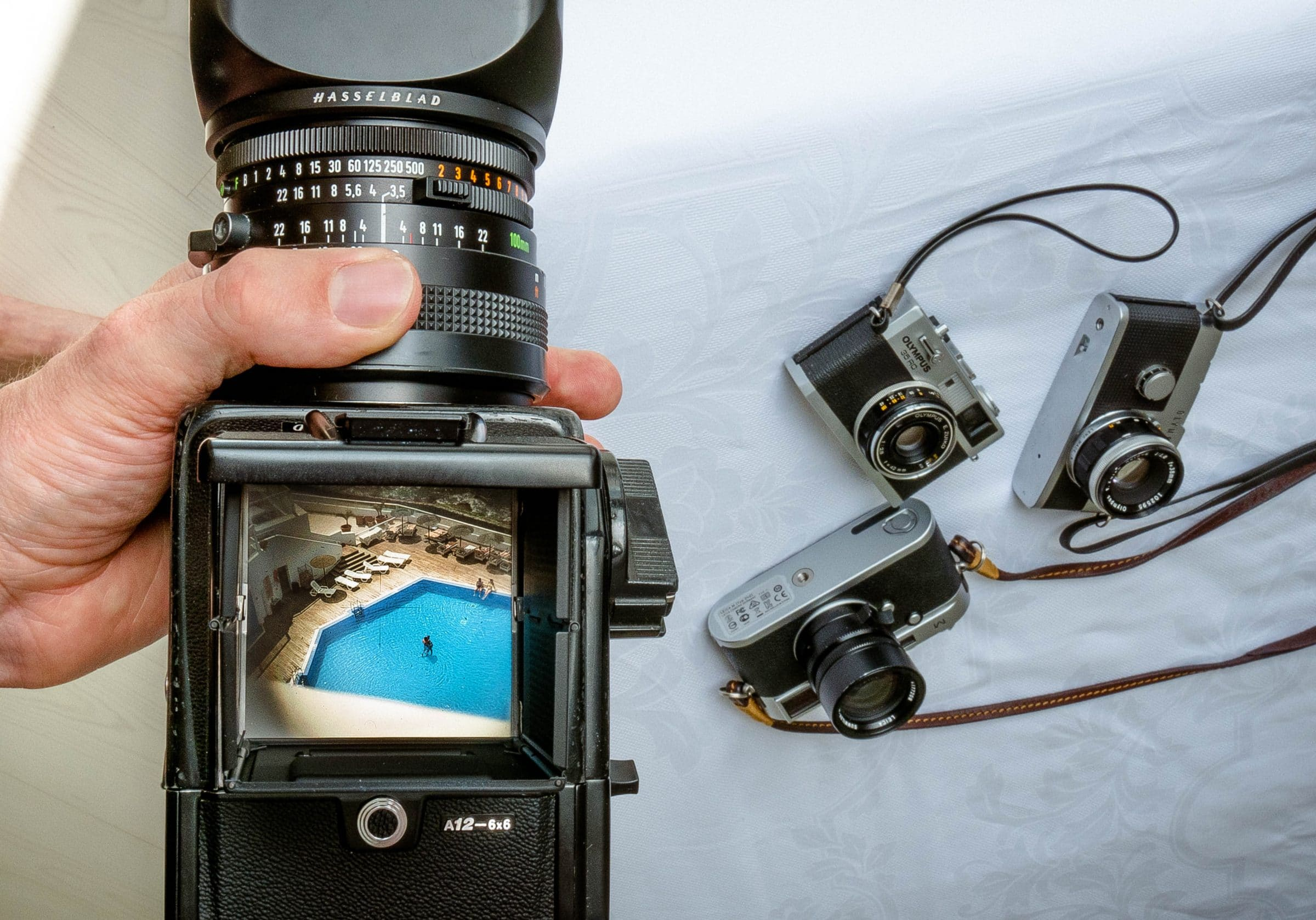 Hasselblad, Leica M, Olympus 35 RC, Olympus Pen F cameras - silver cameras